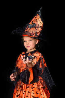 Child in halloween costume of witch holding spider, isolated on black stock vector