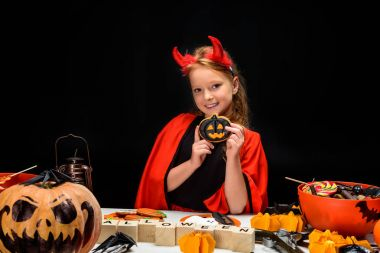 little devil with halloween sweets