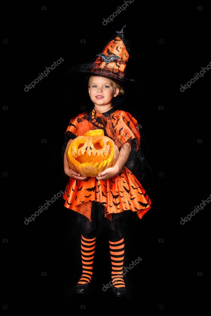 child in halloween costume of witch