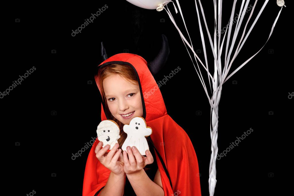 child in costume of devil with cookies
