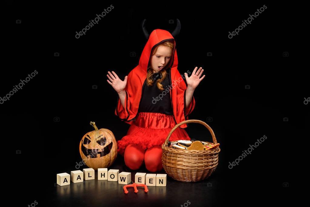 shocked child in costume of devil