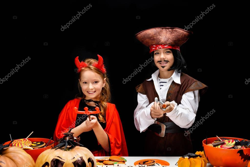 children in halloween costumes of devil and pirate