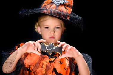 child with halloween bat cookie