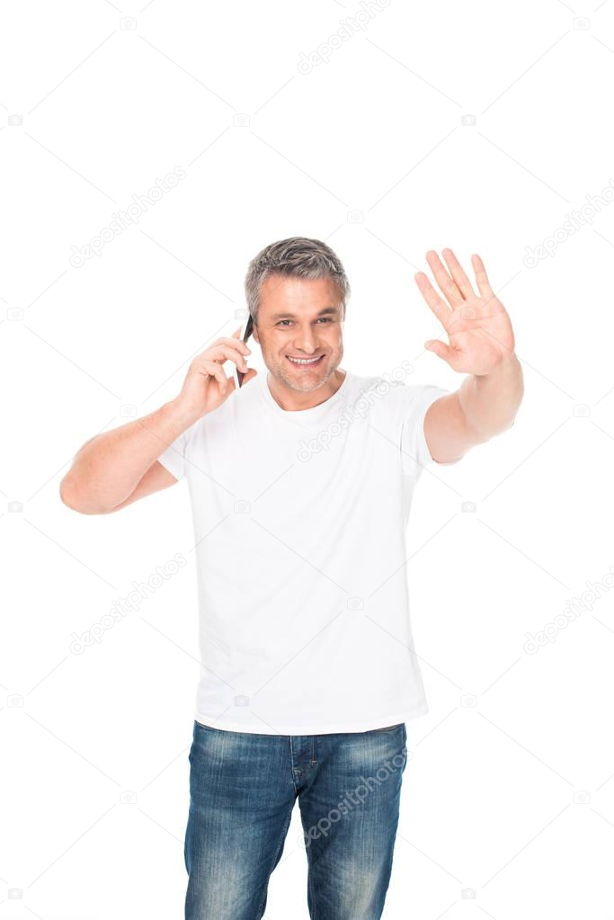 man waving and using smartphone