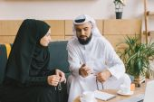 Photo  muslim man showing smartphone to woman