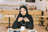 Muszlim nő ül a café