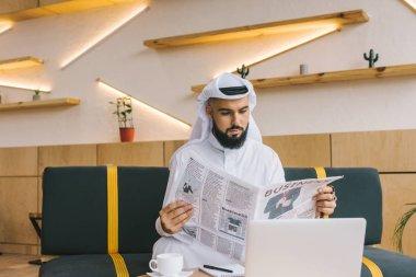 muslim businessman reading newspaper