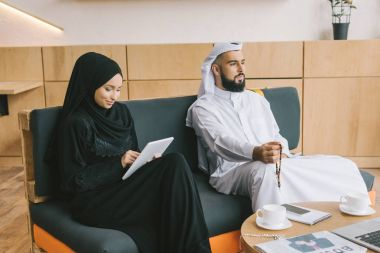 muslim couple sitting on couch