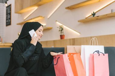 Happy muslim woman talking by phone with shopping bags in cafe stock vector