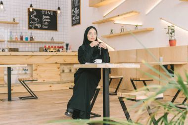 Muslim woman with prayer beads in cafe