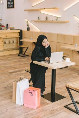 muslim woman using laptop in cafe