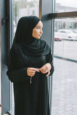 muslim woman looking at window