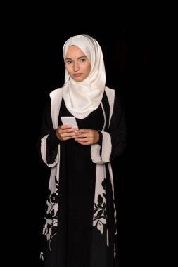 Muslim woman in traditional clothing using smartphone isolated on black stock vector