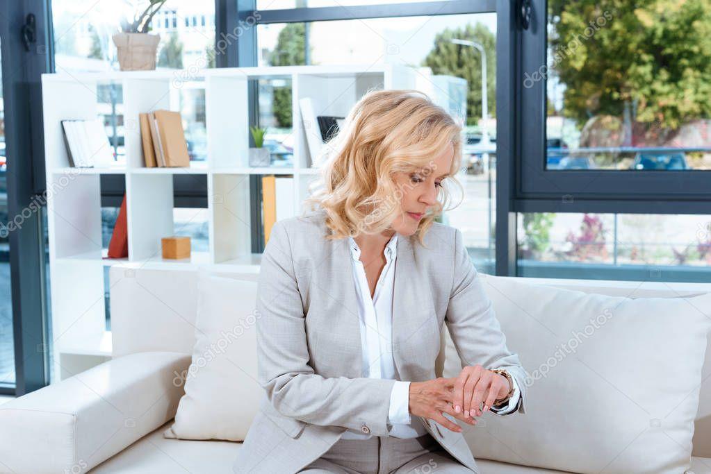 businesswoman checking wristwatch