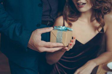 man presenting gift to girlfriend