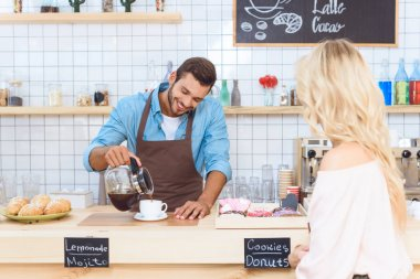 barista pouring coffee to woman