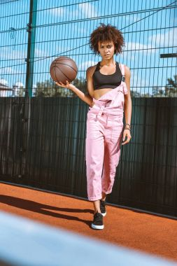 Young african-american woman in sports bra and pink overalls holding basketball ball in her hand stock vector