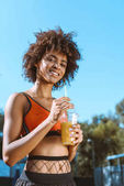 fit african-american woman drinking juice