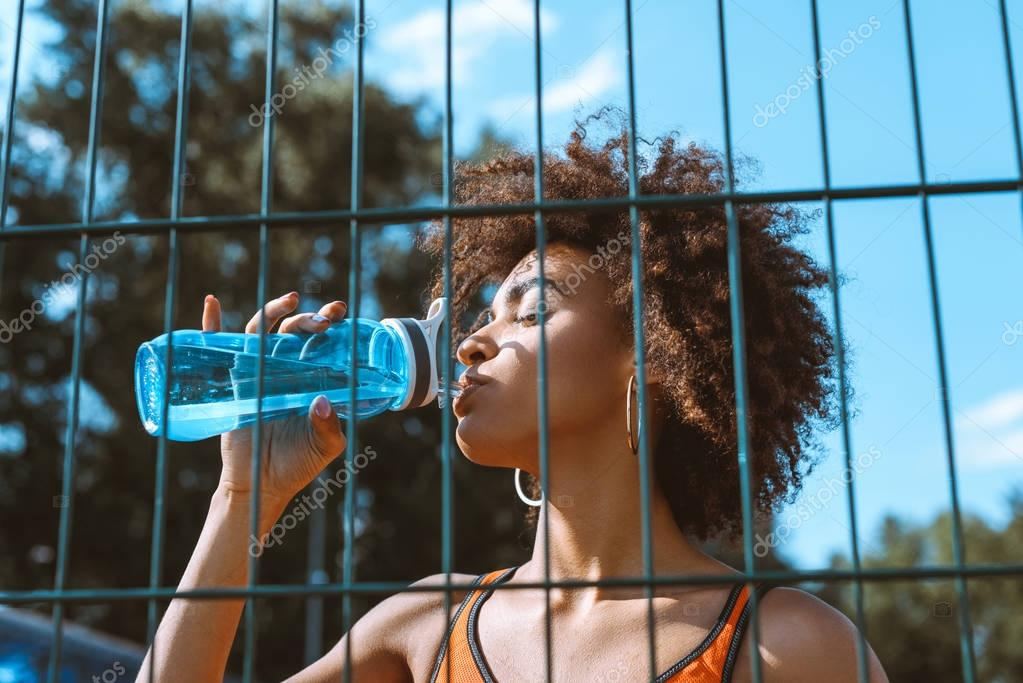 fit african-american woman drinking water