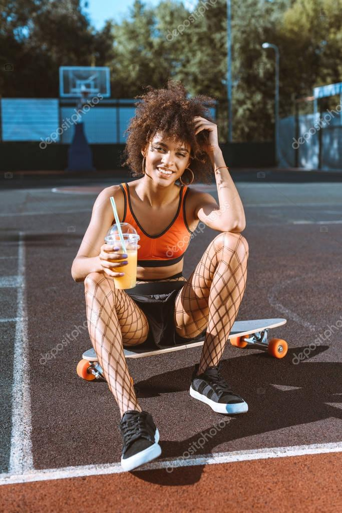 african-american woman on longboard with juice