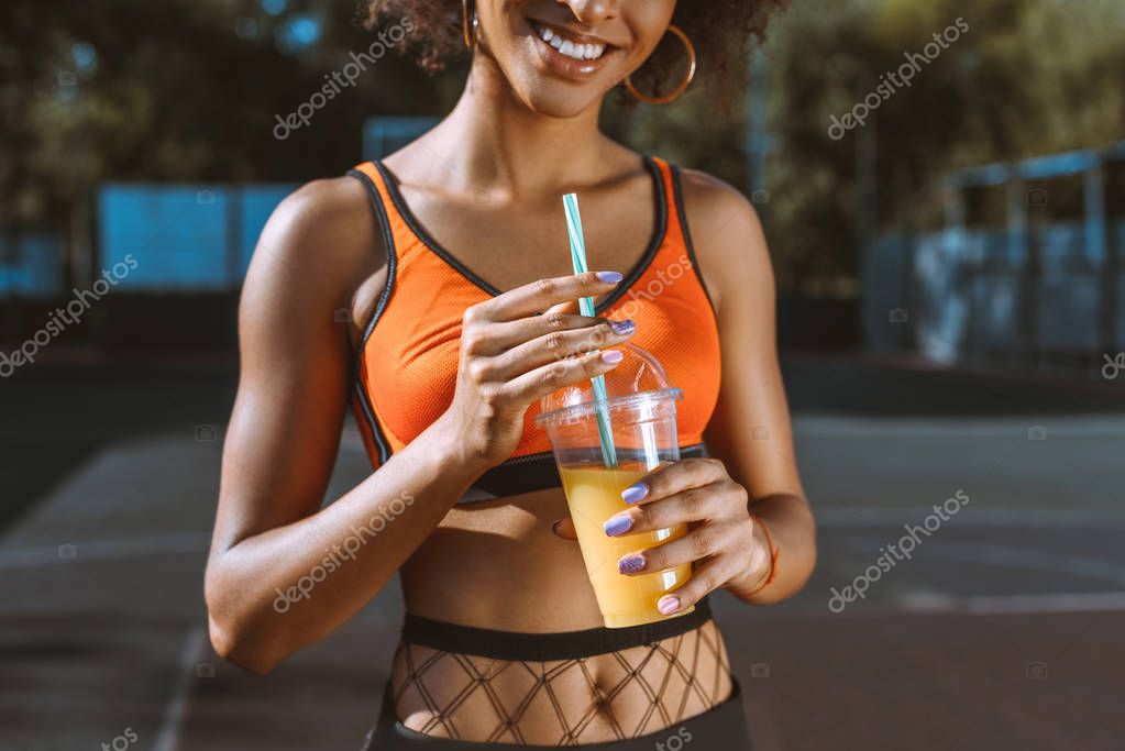 athletic african-american woman drinking juice