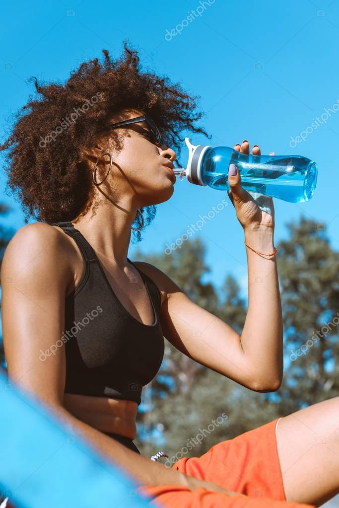 african-american woman drinking from water bottle