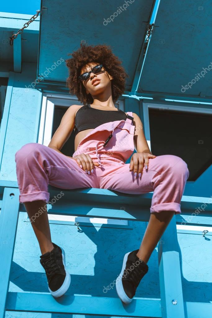 african-american woman sitting on fence