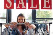 junge Frau wählt Kleidung in Boutique
