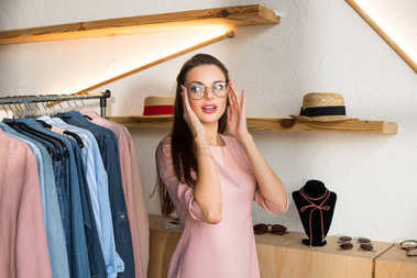 girl choosing glasses in boutique