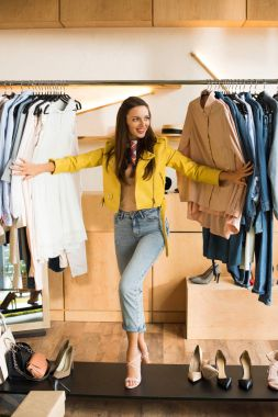 Beautiful smiling young woman choosing clothes in boutique stock vector