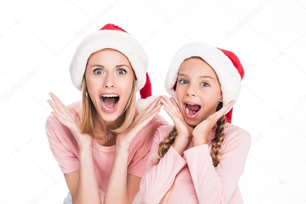 excited mother and daughter in santa hats