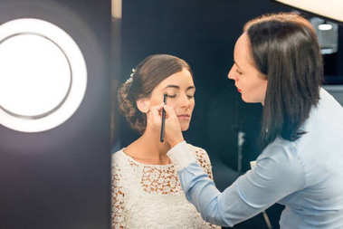makeup artist applying eye shadows