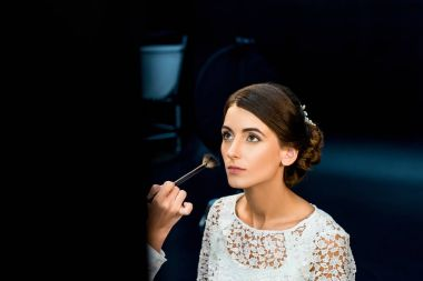 Beautiful woman looking away while makeup artist applying powder in beauty studio stock vector