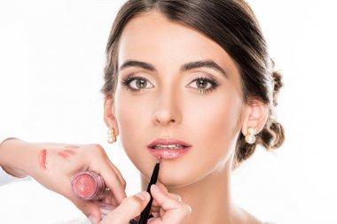 makeup artist applying lipstick on model