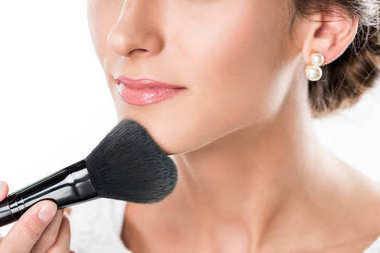 makeup artist applying powder