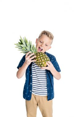 boy biting pineapple