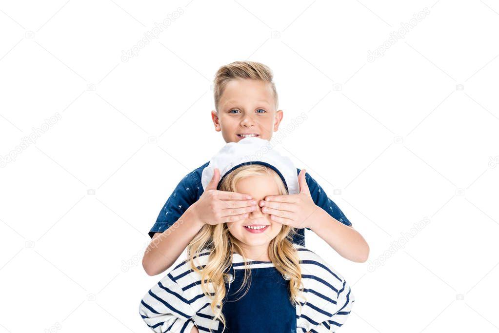 Boy closing eyes of sister