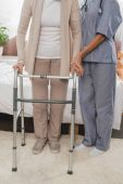 zdravotní sestra a starší pacient s Walkerem