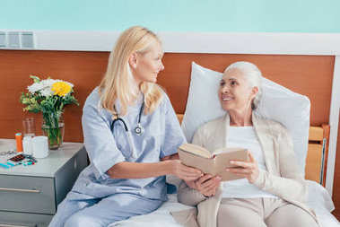Nurse and senior woman reading book and smiling each other at nursing home stock vector