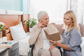 Fotografie zdravotní sestra a starší pacient s knihou