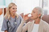 Sestra dávat lék na starší pacient