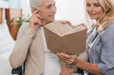 nurse and senior patient with book
