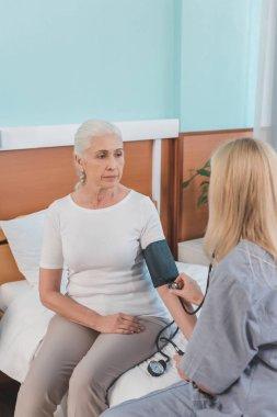 nurse measuring blood pressure to patient