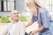 Fotografie zdravotní sestra a starší žena ve vozíku