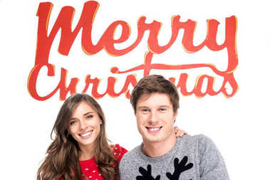couple with merry christmas lettering