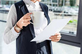 businesswoman holding paperwork and cup