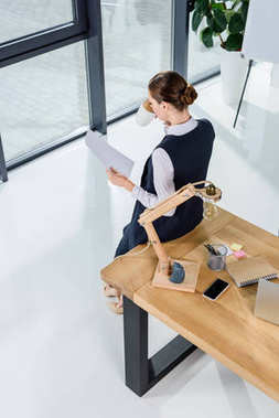 businesswoman with paperwork drinking coffee