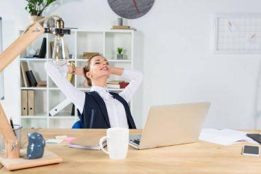 businesswoman sitting with hands behind head