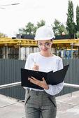 Fotografie Geschäftsfrau auf Baustelle hält Ordner