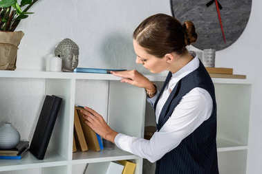 businesswoman looking at books on shelf